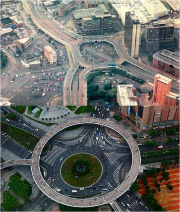 (Top: Birmingham's Masshouse Circus roundabout, part of the inner-city ringroad that famously impeded the city's growth. Bottom: This pedestrian roundabout in Lujiazui, China, constructed over a busy road junction, is a large-scale city infrastructure that balances the need to support traffic flows through the city with the importance that Jane Jacobs first described of allowing people to walk freely about the areas where they live and work. Photo by ChrisUK)